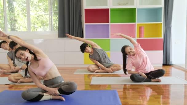 Skupina mladých a předních asijských lidí, kteří se účastní třídy jóga, sedí a protahuje si pas. Skupinový styl sportu.