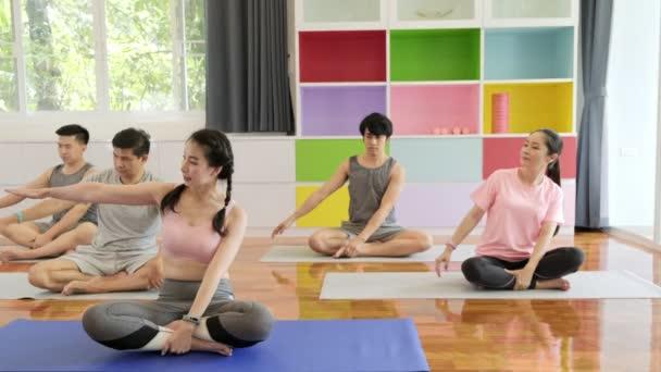 Csoport fiatal és idősebb ázsiai emberek jóga osztály, leült és stretching jobb karját. Csoportos sportéletmód.