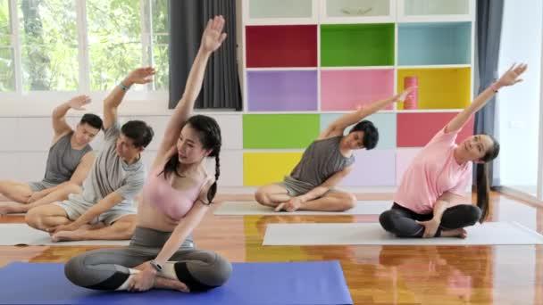 Skupina mladých a předních asijských lidí, kteří se účastní třídy jógu, sedí a roztahuje pravou paži a couvne. Skupinový styl sportu.