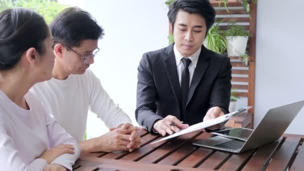 Asijský starší pár, který sedí s finančním poradcem. Dívám se na papíry a chystá se podepsat. Koncept přípravy na důchodové zabezpečení.