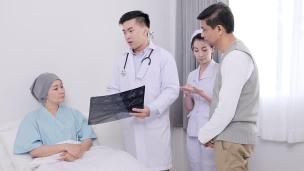 asiatische Seniorin liegt mit Arzt, Krankenschwester und ihrer Frau im Bett und spricht mit Röntgenfilm über ihre Krankheit.