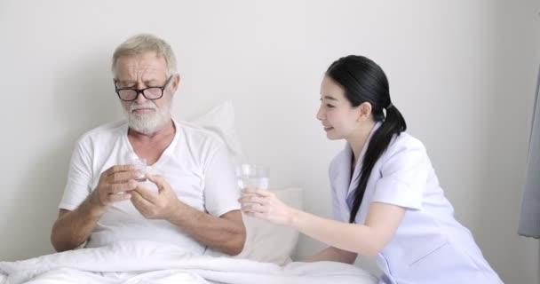 Fiatal ázsiai nővér ad tablettákat vízzel magas rangú beteg