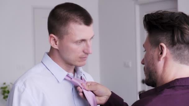 Schwuler Mann hilft seinem Freund beim Anziehen