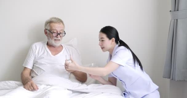 Mladá Asijská ošetřovatelka dává léky s vodou na staršího pacienta