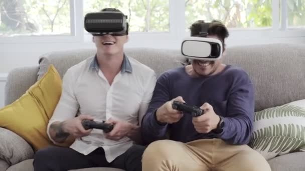 Kaukázusi meleg pár játszik videójáték a joystics otthon és a virtuális valóság szemüveges