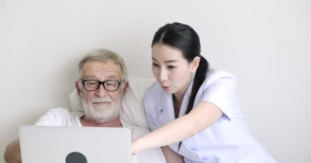 Mladá Asijská ošetřovatelka a dospělý pacient sledují něco na přenosném počítači