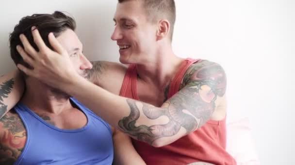 Kavkazský gay pár leží na posteli, objetí a líbání