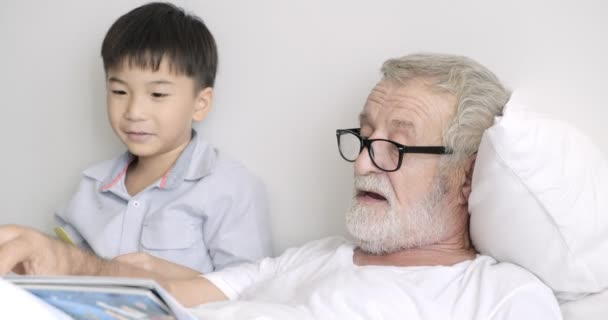 Old mature man playing with toy planes and reading book with his grandchild in clinic
