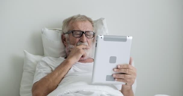 Starý asijský muž leží na posteli a používá počítač Tablet PC na klinice