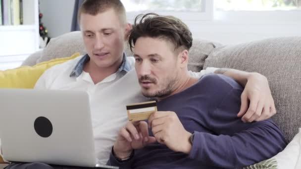 Kaukasisches schwules Paar erledigt Online-Einkäufe auf Laptop mit Kreditkartencomputer zu Hause