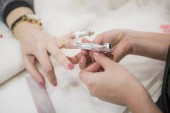 Photo close-up shot of female hands at manicure process in beauty salon