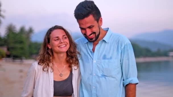 Fiatal, szép párok egy ölelés a tengerpart mentén a naplemente. A fickó és a lány egy trópusi szigeten a mézeshetek.