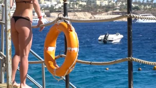 Sicherheitsausrüstung, Rettungsring und Frauengesäß auf Meeresgrund auf dem Holzsteg am Strand. 120fps