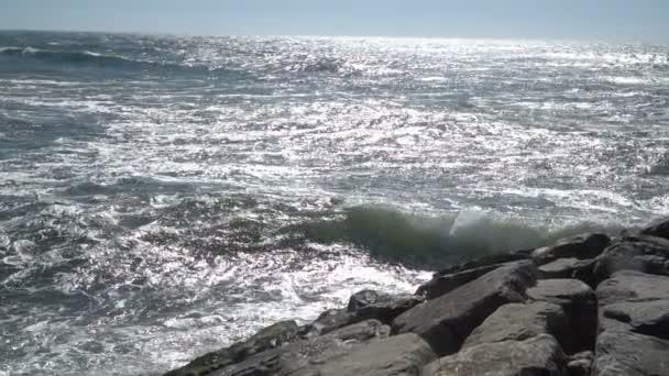 Kilátás a gyönyörű óceán homokos strand a kék hullámok gördülő a part, sziklák jelen.
