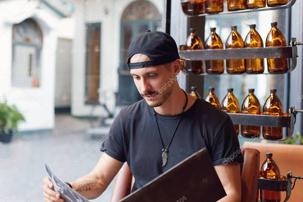 Close up portrait of young and popular food blogger attentively reading menu of brand new restaurant, being invited to taste fusion cuisine and write public report about grand opening of trendy place.