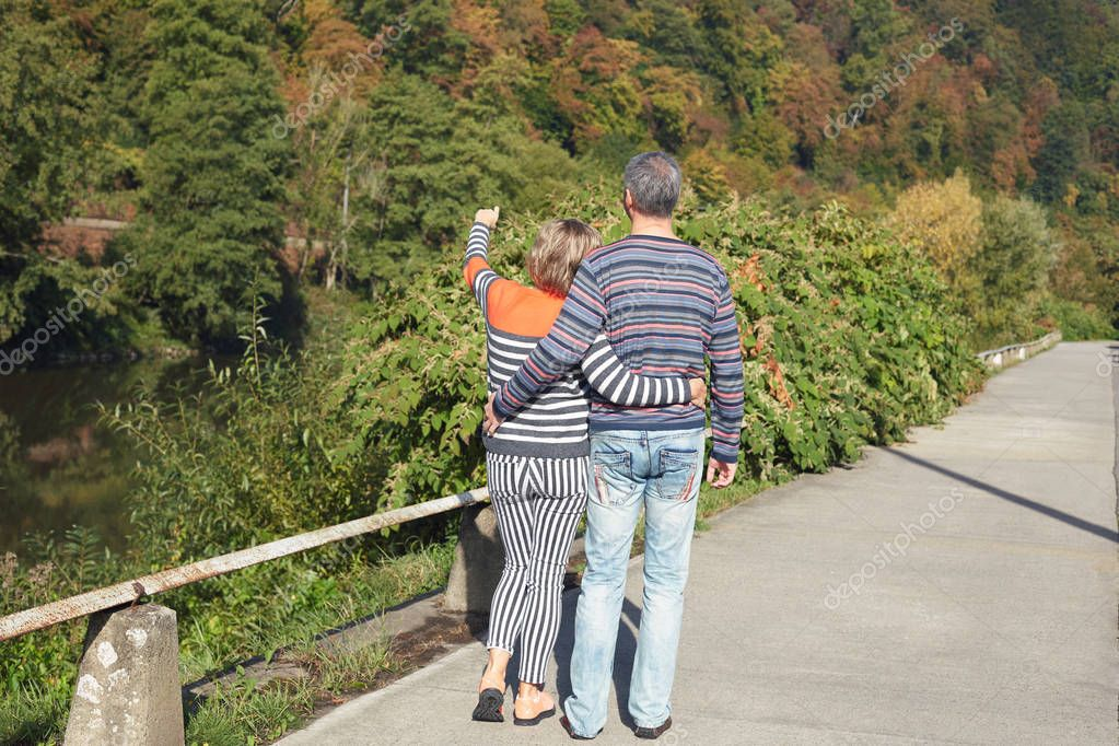 Back view of blond woman and Caucasian mature man have outdoor walk on good summer day, stand closely, lady points into distance as notice beautiful bird in forest. Lifestyle and relationship concept.
