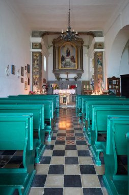 Virgin of the Snow ancient church interior with green pews on mountain top in Prato Nevoso, Italy.