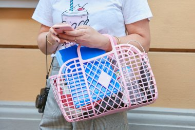 Woman with pink plastic net bag looking at smartphone with white t-shirt with ice cream before Sportmax fashion show, Milan Fashion Week street style on September 22, 2017 in Milan.