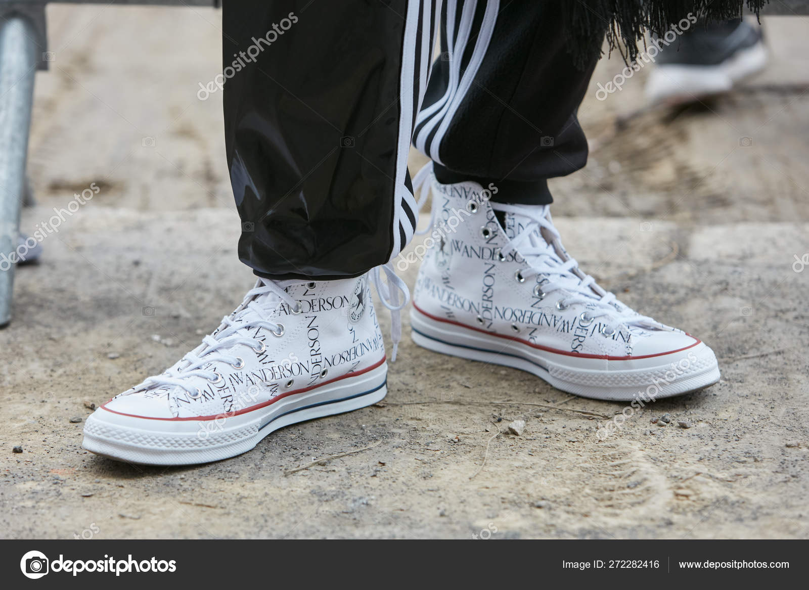 Man with white JW Anderson Converse shoes and black Adidas trousers before  Fendi fashion show, Milan Fashion Week street style on January 15, 2018 in  ...