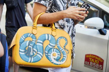 Man with yellow bag with blue snake design and white and black floral shirt before Les Hommes fashion show, Milan Fashion Week street style on June 17, 2017 in Milan.