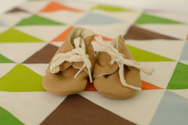 Adorable vintage style girl or boy, soft woolen shoes or booties. Adorable laced up Oxford beige cotton footwear for toddlers or small children set on a colorful cloth with geometric patterns.