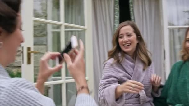 Woman photographing hugging friends in bathrobes