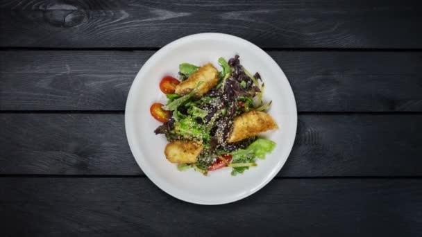 Salát s lososem v trojobalu s hlávkovým salátem a sezamová semínka. Otočí se na černém pozadí dřevěná. Pohled shora
