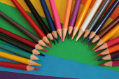 Sada barevných tužek na pozadí listů papíru pro zobrazení maker