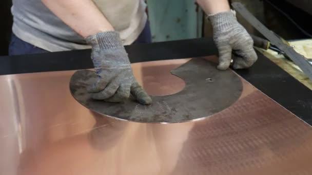 A mester bádogos lerajzolja a jövőbeli termék részleteit a rézlemezből készült vakolatok sablonja szerint. Termelés. Kézzel készített munka.