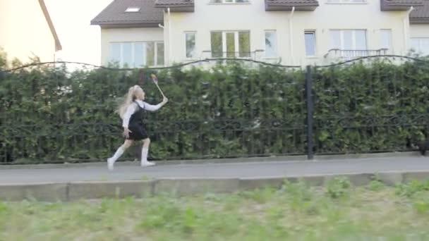 kleines lustiges Schulmädchen in Schuluniform und Aktentasche auf den Schultern, das durch die Gegend läuft. in den Händen des Mädchens mit dem Regenbogen