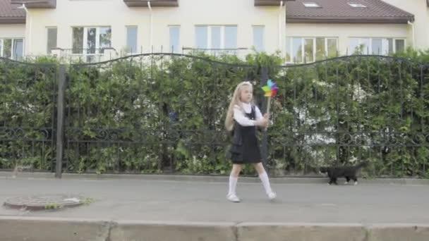 kleines lustiges Schulmädchen in Schuluniform und Aktentasche auf den Schultern, das durch die Gegend läuft. in den Händen des Mädchen Regenbogenspinner, in der Nähe der Straße ist eine Katze