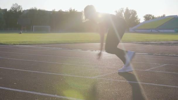 Gyönyörű fitness lány fut alacsony kezdete a stadion. Fiatal sportoló képzés