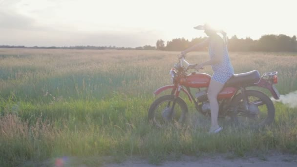 A happy young woman in a hat rides a retro motorcycle and enjoys a ride on a dirt road among the fields and meadows
