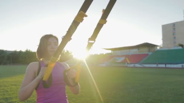 Beautiful fitness girl trains at the stadium. A young athlete is engaged with loops on the field in the football goal