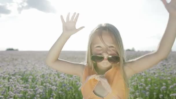 A beautiful, blond girl with her hair dancing in sunglasses on a background of flowers