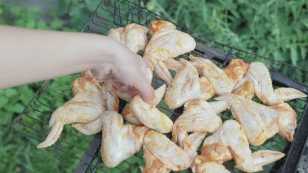 Női kéz helyezi a grill-grill csirke szárny