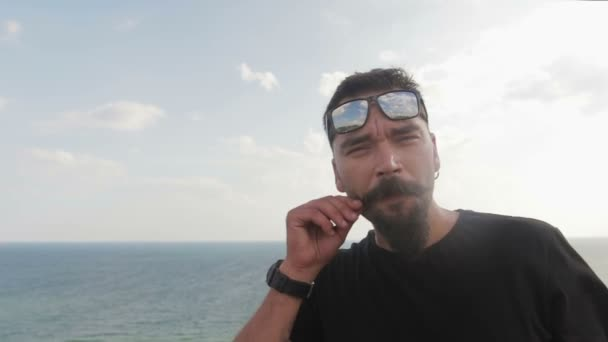 Dude beatnik with mustache, and glasses on the background of the sea. Movember