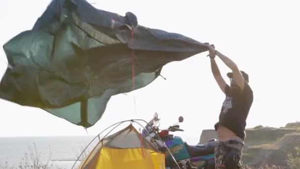 Der Biker stellt das Zelt bei starkem Wind in die Nähe der Motorrad-Enduro