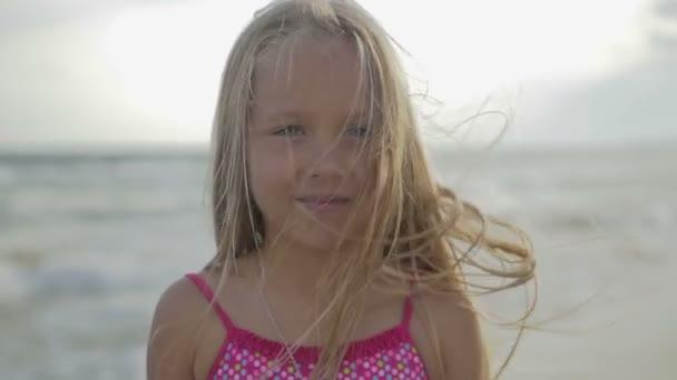 Portrét blond šťastné dcery, kdo sedí na pláži