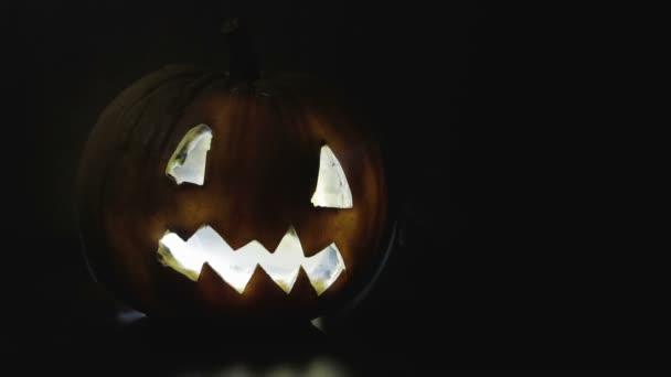 Creepy, scary carved pumpkin on Halloween in smoke