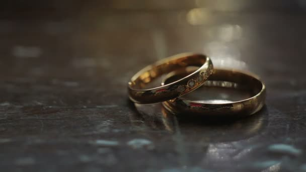 Wedding engagement rings lie on the wooden surface