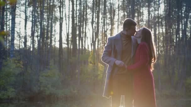Romantický pár stojí a polibky poblíž jezera a mezi nimi paprsky slunce, sluneční světlo