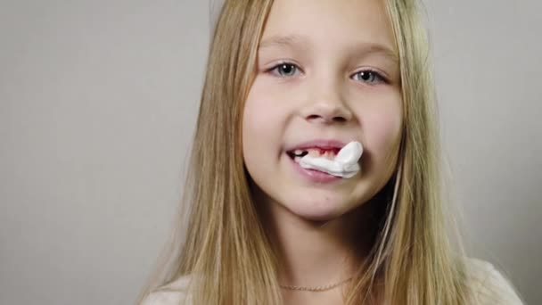 Porträt eines niedlichen lächelnden Mädchens, ein Kind mit einer weißen Serviette im Mund, blutendem Zahnfleisch, Kiefer. Zahnverlust nach Alterskonzept