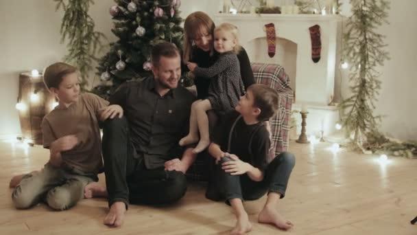 Eine große, eng verbundene Familie von fünf, Vater, Mutter, zwei Söhne und eine Tochter, plaudern in einem Zimmer zu Hause inmitten von Weihnachtsdekorationen und einem Kamin