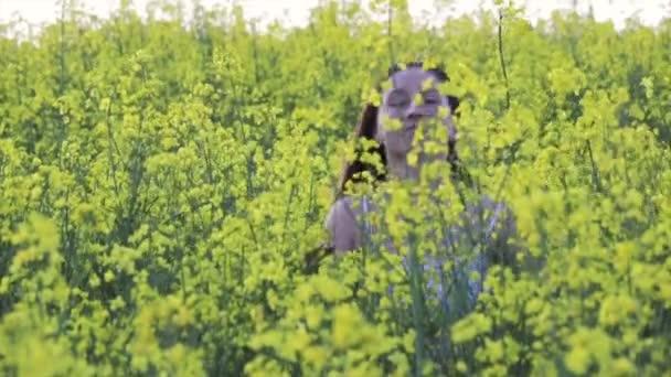 Krásná dívka, co běží ve žlutých květech, semenné pole