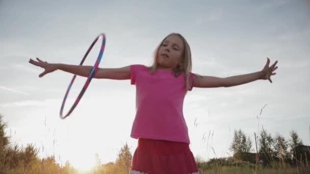 Mädchen in rosa Kleidern dreht Gymnastikreifen