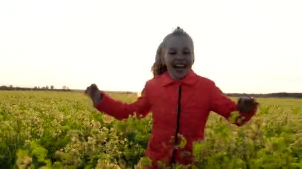 Malá holčička vesele a radostně běží přes pole kvetoucího řepkového semínka, mezi žlutými květy