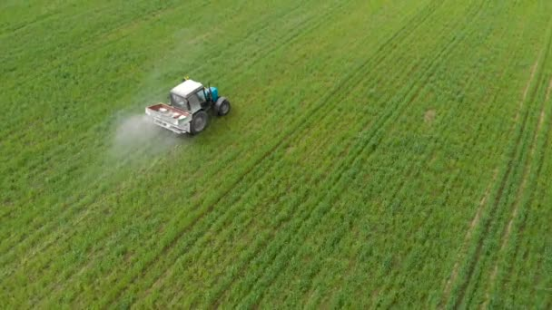 Tractor sprays solid fertilizer in the field, agriculture and agribusiness concepts