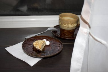 A Cup filled with tea and a plate with dessert near the window.