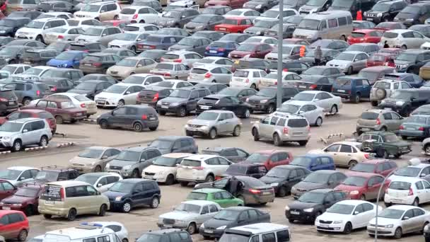 Large parking lot near the shopping center, a lot of cars and hurrying people